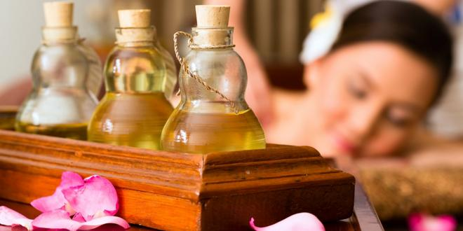A woman with beautiful skin, and bottles of oil